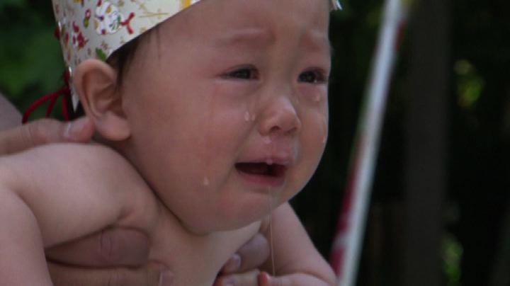 Bebè in lacrime tra le braccia dei lottatori di sumo
