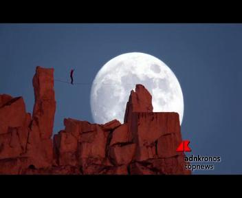 Il funambolo 'tocca' una luna piena gigante