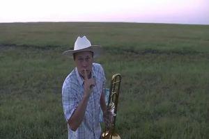 Trombonista suona in mezzo ad un prato, i bovini accorrono ...